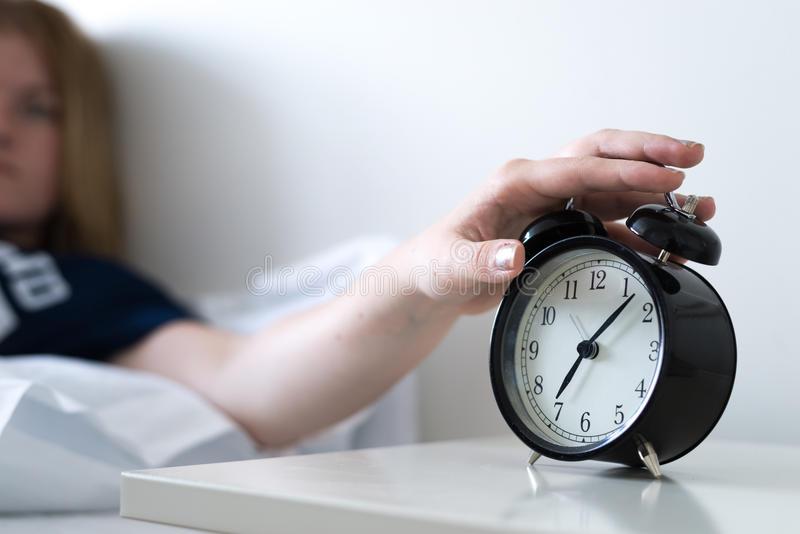 turning-off-alarm-clock-near-bedside-56983178